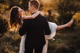 para ślubna, plecami do widza, pan młody niesie panią młodą w stronę słońca