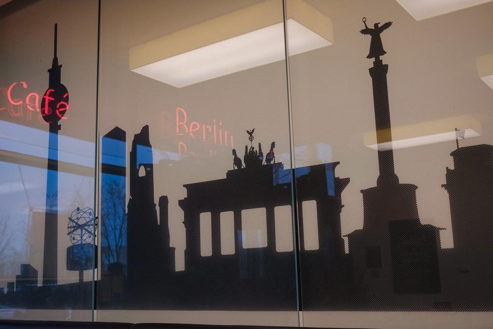 Grafika z symbolami Berlina z odbiciem czerwonego neonu z napisem CAFE oraz Berlin