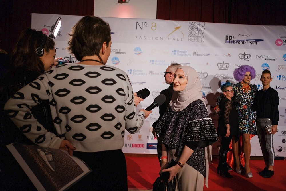 Wywiady z uczestnikami Berlin Fashion Week, pamiątkowe zdjęcia na ściance z drag queen