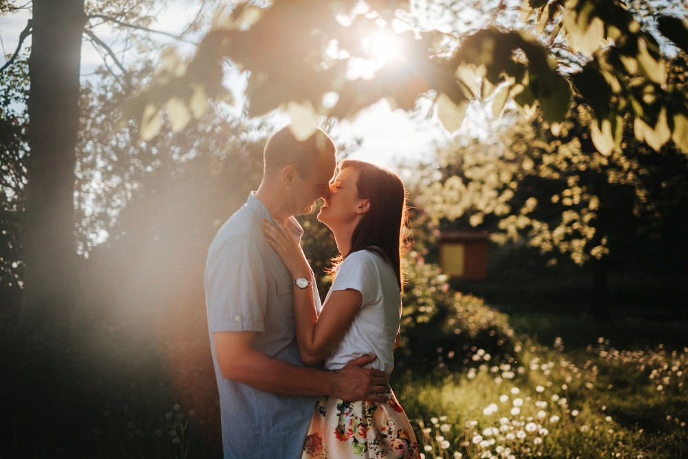 namiętne całusy pod drzewem z ostrym słońcem w kontrze