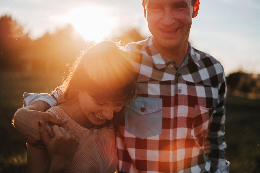 zbliżenie na zakochaną parę, w tle ostre światło słoneczne, całość w ciepłej tonacji