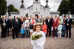 dziewczynka na zdjęciu grupowym z rodziną po mszy z okazji pierwszej komunii świętej
