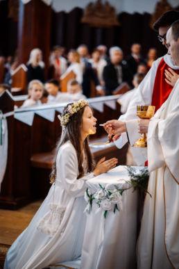 Wiktoria przyjmuje od księdza pierwszą komunię świętą