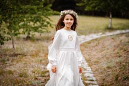 Sesja z okazji Pierwszej Komunii Świętej Wiktorii - dziewczynka spacerująca ścieżką
