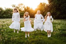 dziewczynki w podskoku zdjęcie z okazji pierwszej komunii świętej