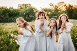 dziewczyny w strojach komunijnych z dmuchawcami