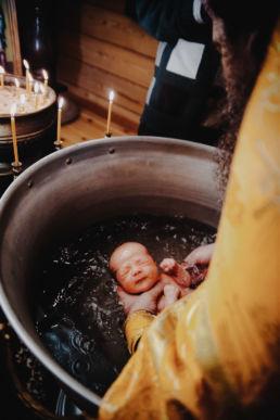 batuszka zanurza dziecko w wodzie podczas chrztu prawosławnego