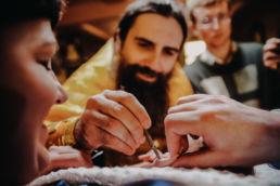 ksiadz prawosławny smaruje pędzelkiem dłoń chrzczonego dziecka