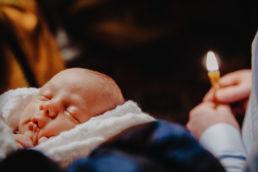główka śpiącego dziecka z zapaloną świecą w tle