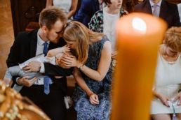 rodzice trzymają na rękach dziecko po ceremonii chrztu świętego