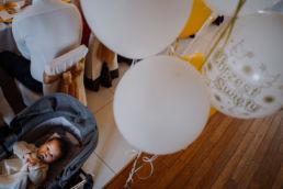 dziecko leży w wózku, nad nim balony z napisem Chrzest Święty