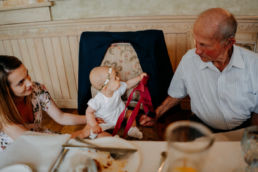 dziecko podaje krawat pradziadkowi