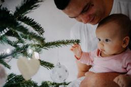 dziecko trzymane przez tatę dotyka drzewka choinkowego