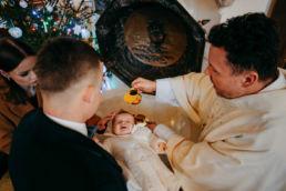 ksiądz polewa główkę dziecku podczas chrztu w Białymstoku