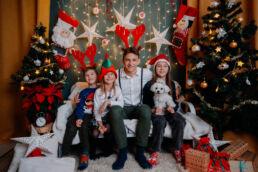 dzieci na kanapie podczas sesji fotograficznej w studio z okazji świąt bożego narodzenia